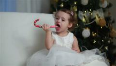 Little cute girl eating a piece of candy on the eve of Christmas Stock Footage