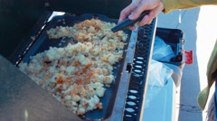 Woman cooking potato hash browns while camping Stock Footage