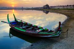 Wooden boat in Ubein Bridge at sunrise, Mandalay, Myanmar - stock photo