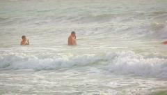 Tourists swimming in the surf at Kamala Beach on Phuket, in southern Thailand Stock Footage