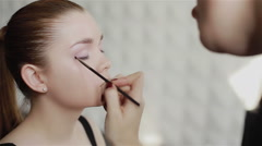 Professional make-up artist feathering light violet eyeshadow on the eyelid. Clo - stock footage