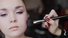 Professional make-up applying blush on cheekbones. Close-up. Front view Stock Footage