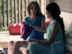 Woman gets gift from her friend on sofa at home NTSC Stock Footage