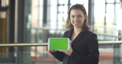 Holding greensreen tablet ipad business person smiling in office - stock footage