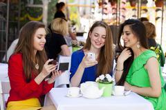 Three happy beautiful girls girlfriend drinking tea in a summer cafe - stock photo