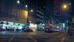Urban intersection with electric street cars and buses in Hong Kong, at night Stock Footage