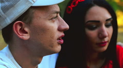 A young couple discusses the latest events in the Park. Close up - stock footage