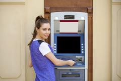 Young woman in summer dress using an automated teller machine Stock Photos
