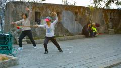 Women participating in Tai Chi training with weapons in a city park in Macau Stock Footage