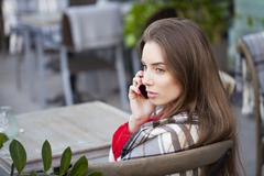 Young beautiful girl sits in summer cafe and calling by phone - stock photo