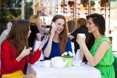 Three happy beautiful girls girlfriend drinking tea in a summer cafe Stock Photos
