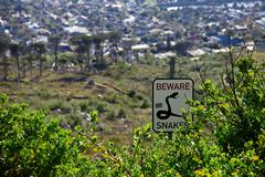 Beware snakes sign post in the bushes of Capetown, Saouth Africa - stock photo