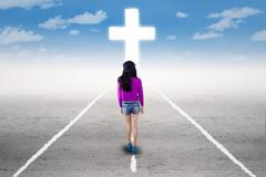 Girl in a spiritual journey with a cross - stock photo