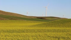 A group of turbine generators in a hilly yellow landscape - stock footage