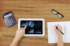 Worker using tablet to analyze business charts Stock Photos