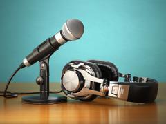 Microphone and headphones. Audio recording or radio commentator concept. - stock illustration