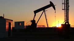 Beautiful sunset silhouette of an industrial oil field pump - stock footage