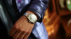 Man male businessman clock in suit standing at the window looking at his watch Stock Footage