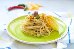 Spaghetti with marinated anchovy, zucchini and zucchini flowers Stock Photos