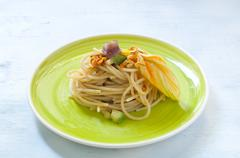 Spaghetti with marinated anchovy, zucchini and zucchini flowers - stock photo