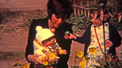 1974: Single family mother with two children relaxing in rose garden. - stock footage