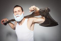 Handsome young hipster guy threatens with axe - stock photo