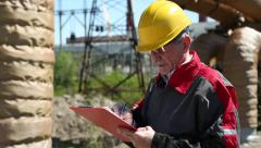 Engineer builder in yellow helmet writes down information about object Stock Footage