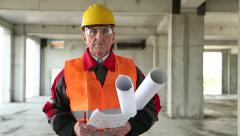 Engineer builder in yellow helmet and orange vest stands at construction site Stock Footage