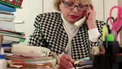 Blond business woman  talking on phone, writing down information - stock footage