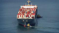 Tug Boats Pushing Freighter Around At Sea - stock footage