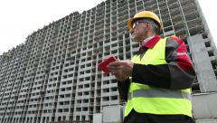 Engineer in yellow helmet stays with telephone near unfinished house Stock Footage