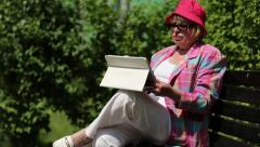 Woman in red hat, jacket, white trousers sits on bench and switches on device Stock Footage