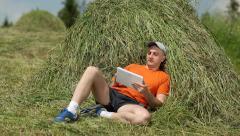 Man in orange T-shirt lying on haystack, watching gadget Stock Footage