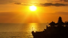 Sun going down over bali sea temple tanah lot time lapse zoom out Stock Footage