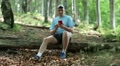 Man sitting on log, talking on skype, showing surround nature HD Footage