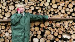 Woman in green slicker standing near timber, talking telephone Stock Footage