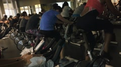 Group of people pedaling fast during a spinning class Stock Footage
