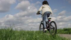 4K Young girl rides into a play area, in slow motion, shot on Red Epic Dragon Stock Footage