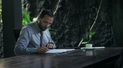 Young businessman writing notes in documents sitting by table at home Stock Footage