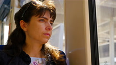 Woman sitting in a moving train and looking outside, London, United Kingdom Stock Footage