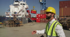 Stock Video Footage of Business team standing at a commercial dock inspect shipment for delivery.