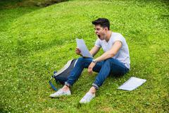 Young Bored, Tired Male Student Studying in City Park - stock photo