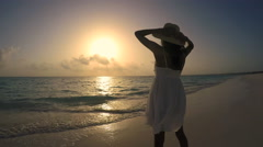 Young ethnic female in white dress on sunrise beach Stock Footage