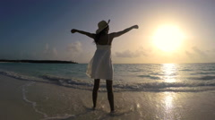 Young ethnic female in white dress dancing on sunrise beach Stock Footage