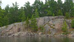 Canoeing past rocky shore with evergreen trees. Ontario, Canada. Stock Footage