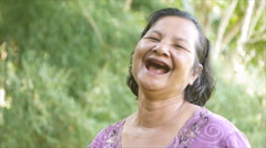 Thai woman laughing happily in garden Stock Footage