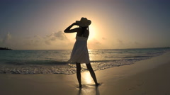 African American girl in white sundress barefoot on sunset beach Stock Footage