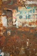 Stock Photo of Weathered paper on Rusty Metal Wall in Thailand, Closer