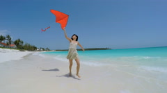 Smiling Asian Chinese girl playing with red kite on beach Stock Footage