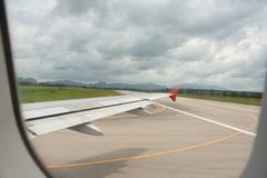 Wing view and taxi way before takeoff On cloudy days Stock Photos